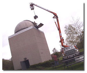 new telescope being hoisted into observatory by crane