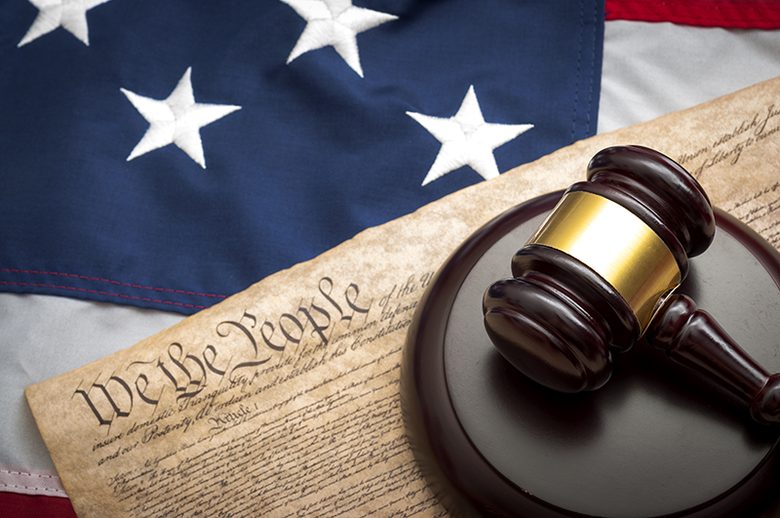 Symbols of the American justice system: a U.S. flag and a gavel