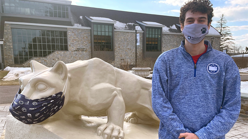 Student Government Association President Larry Corridoni stands in front of the Nittany lion shrine at Penn State Wilkes-Barre.