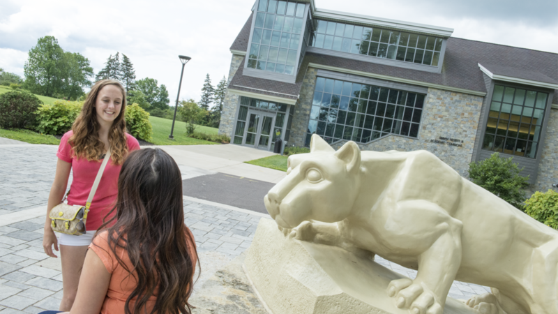 Two female students having a conversation in front of the campus Lion Shrine, in front of the Academic Commons building