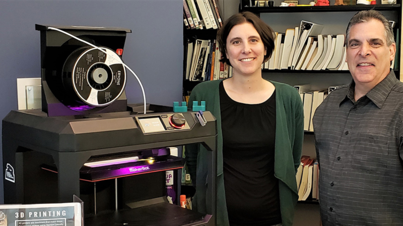 Jonathan Pineno (Friedman Art Gallery director) and Megan Mac Gregor (librarian) standing in front of the Nesbitt Library's 3D printer; two of the small green widgets are sitting on top.