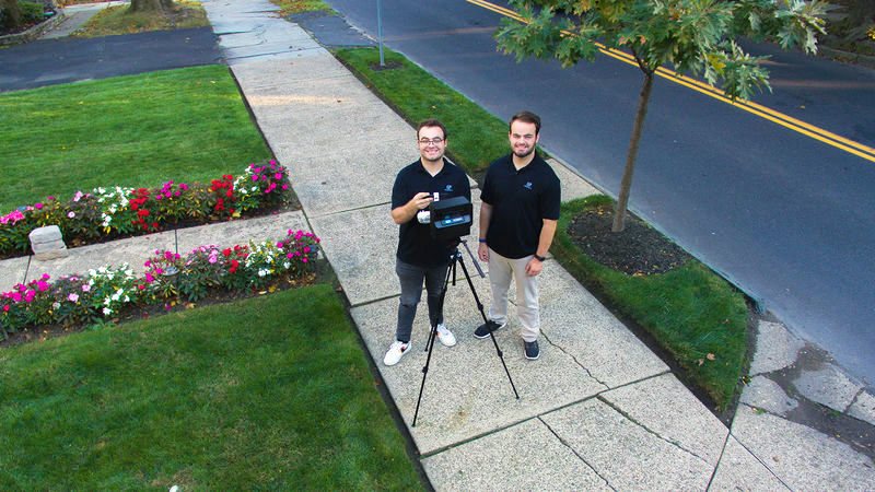 Matthew and Patrick Nelson standing with a 360-degree camera and tripod
