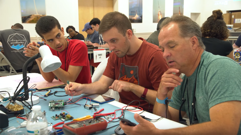 Professor Tim Sichler and student Pablo Franco Almonte working with teammate Christopher Handgis to test a payload sensor