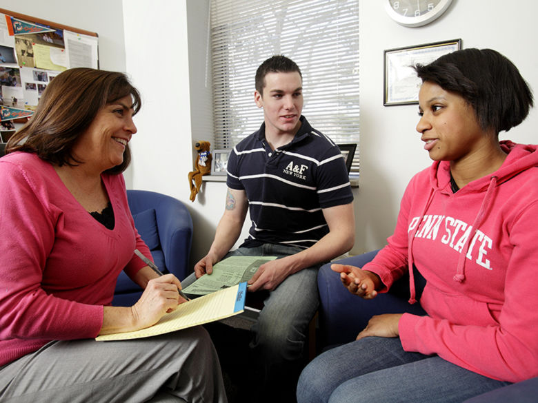 Professor in a discussion with two students in her office