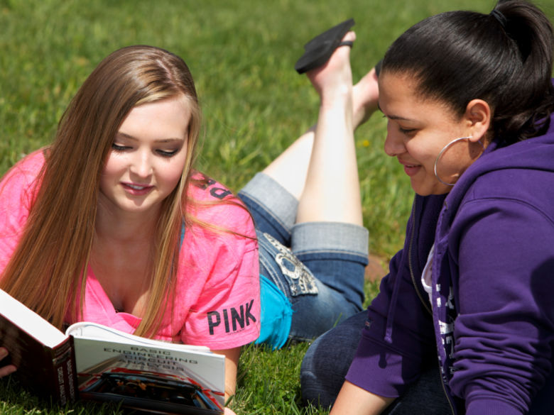Two students studying and enjoying the outdoors