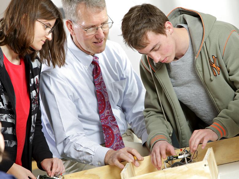 Professor coaches student working on robotics project