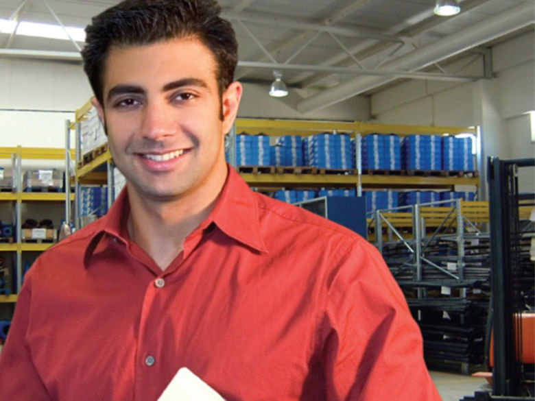 Smiling young man with clipboard in a manufacturing environment