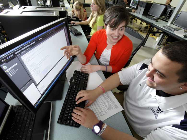 Student and faculty member working side-by-side in front of a computer