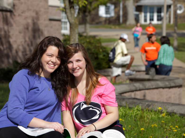 Two female students studying together outside in the sunshine