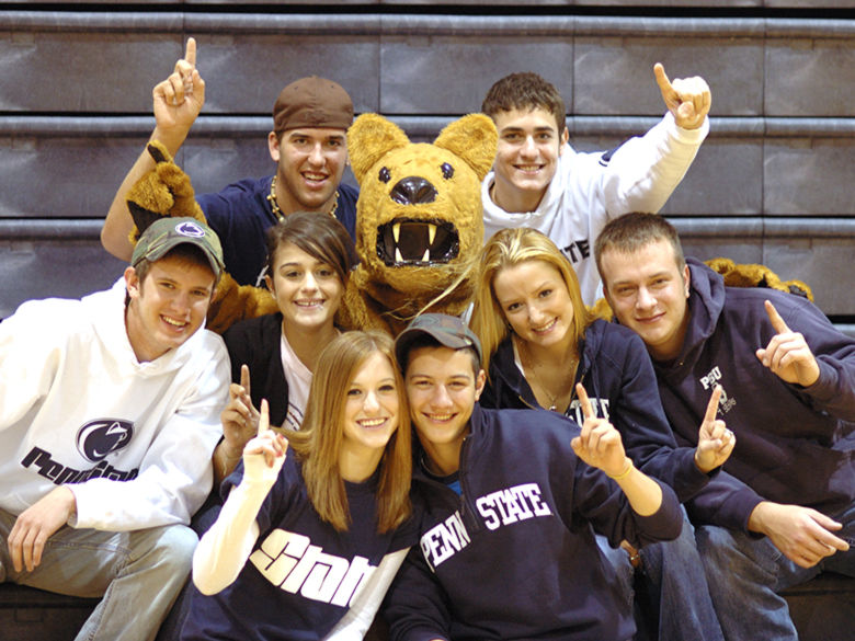 "Students gathered around the Nittany Lion mascot, facing forward and holding up their index fingers in the ""we're number one"" sign"