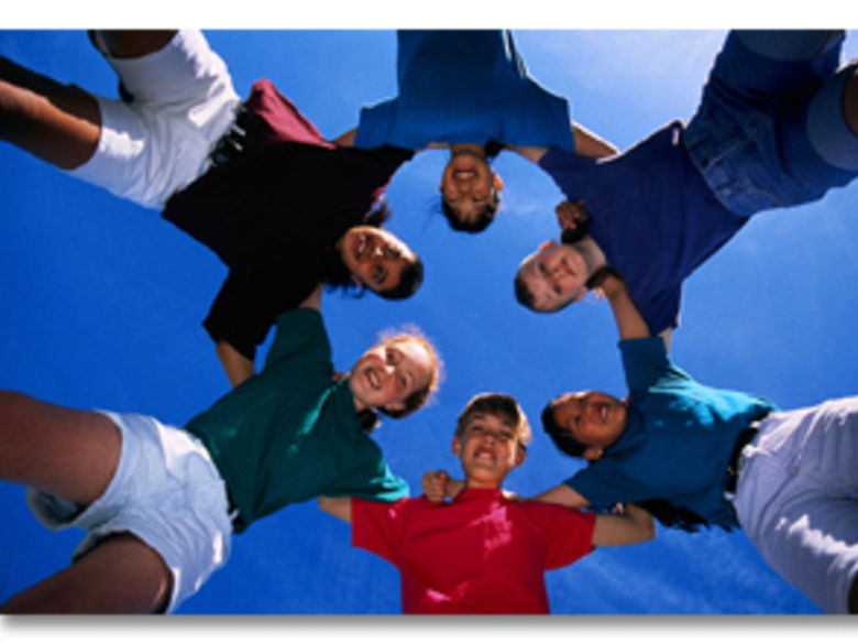 young people in a circle with arms linked (looking down at the camera pointed up in the center)