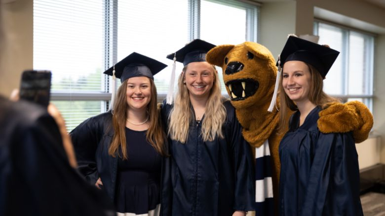 Three female graduates pose with Nittany Lion mascot