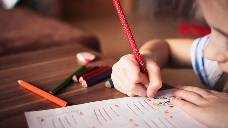 Small child at her desk in a classroom writing in pencil on a piece of paper