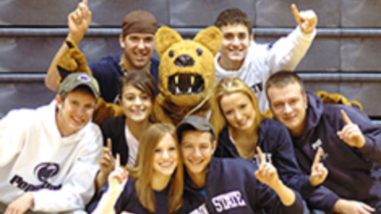 "Student Lion Ambassadors gathered around the Nittany Lion mascot, signaling ""We're number 1!"" by holding up their index fingers."