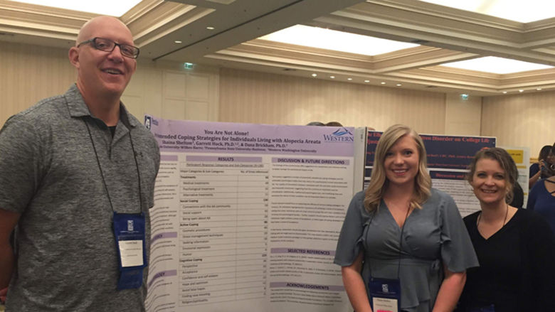 Dr. Garrett Huck, Shaina Shelton, and Dr. Dana Brickham pose in front of their poster
