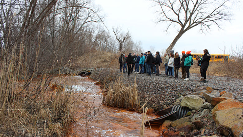 Students looking at a creek filled with brown sediment during a tour of Brownfields
