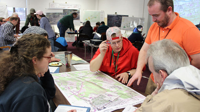 Students in a classroom gathered around a surveying map as the instructor points out an item of interest