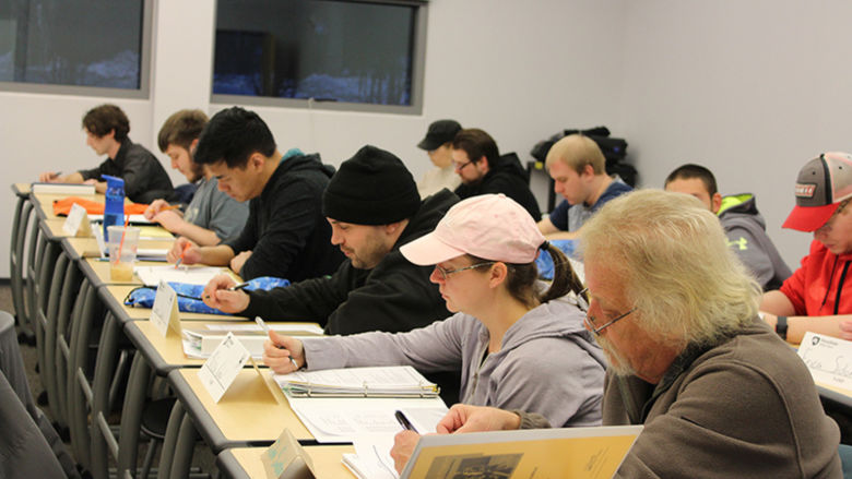 Students seated in a classroom, individually taking notes