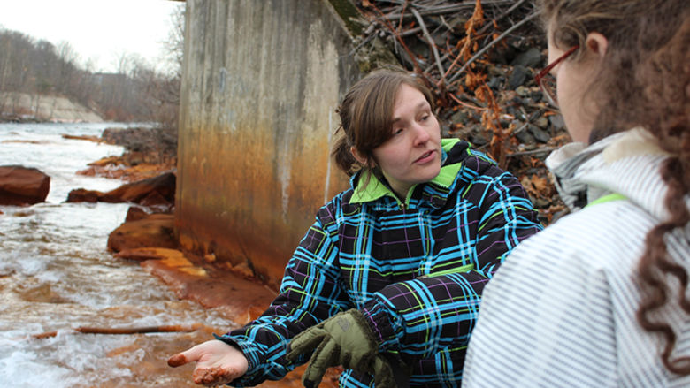 Instructor points out sediment in stream from runoff