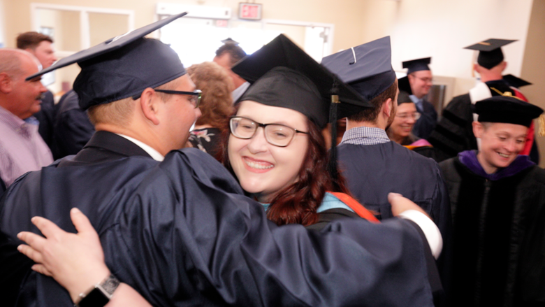 Two graduates hugging each other immediately after the commencement ceremony