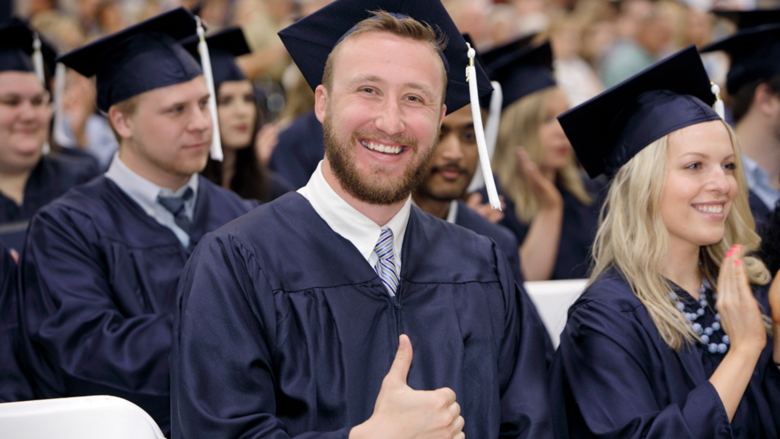 "Grinning graduate in academic robe flashing the ""thumbs up"" sign at the camera"